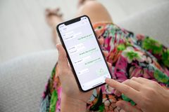 Woman holding iPhone X with social networking service WhatsApp. Alushta, Russia - September 27, 2018: Woman holding iPhone X with social networking service stock photo