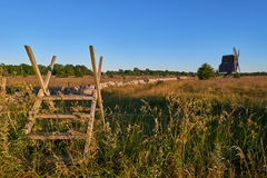 Alvar limestone moor with fence and mill at sunset. Alvar limestone moor with fence and old windmill in sunset at Isle if Oeland, province Kalmar, Sweden Royalty Free Stock Images