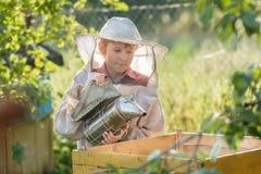 Alveare di fumo dell'apicoltore adolescente nell'iarda dell'ape Fotografia Stock