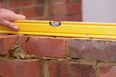 A alvenaria que verifica tijolos é nível Fotografia de Stock