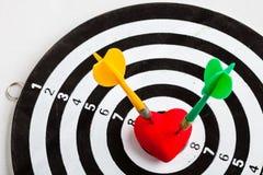 Alvo branco preto com os dois dardos no símbolo do amor do coração como o bullseye Foto de Stock