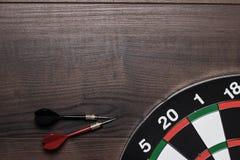 Alvo e dois dardos na tabela de madeira Imagem de Stock Royalty Free