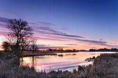Alvoreça com nuvens cor-de-rosa sobre uma lagoa selvagem cercada por árvores na manhã do outono Fotos de Stock Royalty Free