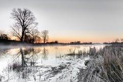 Alvorecer cromático sobre uma lagoa selvagem cercada por árvores na manhã do outono Imagens de Stock Royalty Free