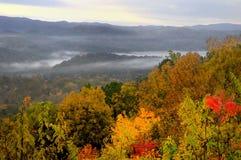 Alvorecer na via pública larga e urbanizada ocidental, montanhas fumarentos dos montes, TN EUA. Fotografia de Stock