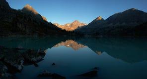 Alvorecer nas montanhas no lago Imagens de Stock