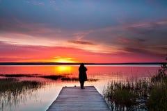 Alvorecer sobre um lago quieto Nascer do sol, silhueta de um homem que está sobre fotografia de stock royalty free