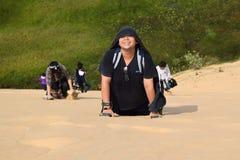 Alza de la gente en la duna de arena Imagenes de archivo