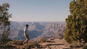 Alzas turísticas jovenes activas felices del hombre que caminan por la cámara al lado en el paisaje épico del calor del verano de metrajes