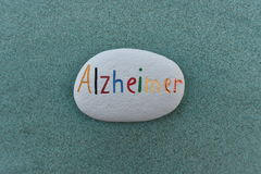 Alzheimer disease name painted on a stone. Alzheimer, mental health problem, conceptual painted stone over green sand Stock Photo
