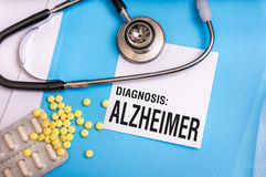 Alzheimer word written on medical blue folder with patient files. Pills and stethoscope on background stock photography