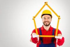 Amélioration de l'habitat - bricoleur avec la règle formée par maison dans des mains dessus photo libre de droits