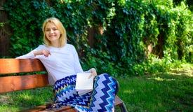Améliorez votre connaissance Coupure blonde de sourire heureuse de prise de femme détendant dans le livre de lecture de jardin La photographie stock libre de droits