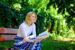 Améliorez votre connaissance Coupure blonde de sourire heureuse de prise de femme détendant dans le livre de lecture de jardin Ma images libres de droits