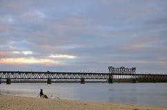 Aménagez en parc au coucher du soleil et au pont au-dessus de la rivière, Kremenchug Photographie stock