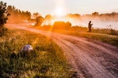 Aménagez en parc, aube ensoleillée avec la route et pêcheur Image libre de droits