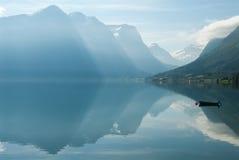 Aménagez en parc avec des montagnes se reflétant dans le lac et le petit bateau, Norvège Photographie stock libre de droits