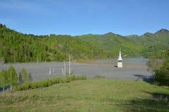 Aménagez en parc avec l'église floded au lac de Geamana dans les montagnes d'Apuseni, Roumanie Image stock