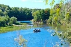 Aménagez en parc avec la rivière et le canoë avec des personnes là-dessus Photos libres de droits