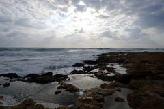 Aménagez en parc avec le beau coucher du soleil sur le littoral avec des pierres en mer et des nuages sur le ciel image libre de droits