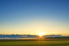 Aménagez en parc avec le lever de soleil, le champ, le ciel et le soleil Photographie stock libre de droits