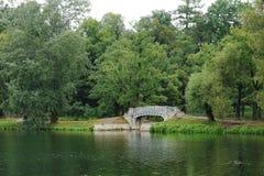 Aménagez en parc avec le vieux pont au-dessus de l'écoulement en parc de palais Image stock