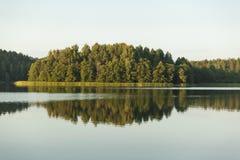 Aménagez en parc avec les arbres et le ciel se reflétant dans le lac Image libre de droits