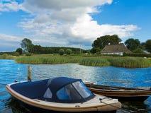 Aménagez en parc avec les bateaux amarrés dans l'eau et le cottage rustique image libre de droits