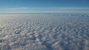 Aménagez en parc de la fenêtre d'avion à une mer massive des nuages dans un ciel bleu Images libres de droits