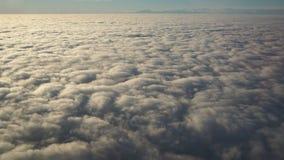 Aménagez en parc de la fenêtre d'avion à une mer massive des nuages dans un ciel bleu Image libre de droits
