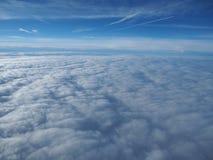 Aménagez en parc de la fenêtre d'avion à une mer massive des nuages dans un ciel bleu Photos libres de droits