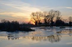 Aménagez en parc sur la rivière au coucher du soleil dans la saison de hautes eaux Image libre de droits