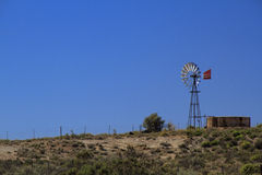 Aménagez le moulin à vent en parc dans le désert avec le ciel bleu Photographie stock libre de droits