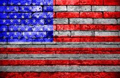 Américas señalan por medio de una bandera en la pared de ladrillo Foto de archivo libre de regalías