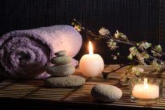 A amêndoa floresce com velas, pedras brancas na esteira de bambu foto de stock