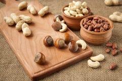 Amêndoas, amendoim do caju, avelã em umas bacias de madeira em de madeira e serapilheira, fundo do saco Foto de Stock