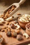 Amêndoas, amendoim do caju, avelã em umas bacias de madeira em de madeira e serapilheira, fundo do saco Fotografia de Stock Royalty Free