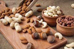 Amêndoas, amendoim do caju, avelã em umas bacias de madeira em de madeira e serapilheira, fundo do saco Fotos de Stock Royalty Free
