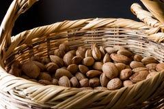 Amêndoas cruas orgânicas frescas com Shell na cesta Foto de Stock