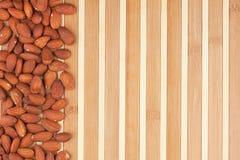 Amêndoas descascadas que encontram-se em uma esteira de bambu Imagem de Stock Royalty Free