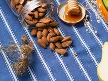 Amêndoas e mel no pano de tabela Imagens de Stock Royalty Free