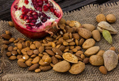 Amêndoas em um fruto do almofariz e da romã Fotos de Stock Royalty Free