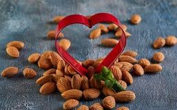 Amêndoas no vermelho sob a forma de um coração, conceito para o dia de Valentim foto de stock royalty free