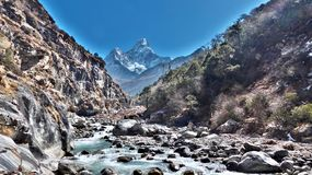 Ama Dablam i bakgrunden, flod mellan berg arkivfoton