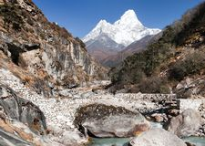 Ama Dablam with stony and wooden bridge above river Royalty Free Stock Images