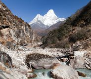 Ama Dablam with stony and wooden bridge above river Royalty Free Stock Photo