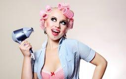 Ama de casa alegre con el hairdryer Imagen de archivo