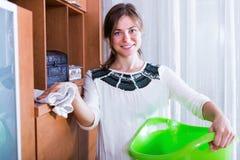Ama de casa alegre con los estantes de la limpieza del trapo Imagen de archivo libre de regalías