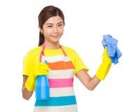 Ama de casa asiática con el espray y la toalla detergentes Fotografía de archivo