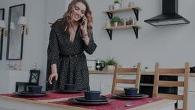 Ama de casa atractiva en vestido negro que llama a sus parientes y huéspedes que esperan Cocina moderna de la luz del día con f metrajes